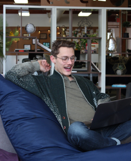 Person sitting on bean bag chair with laptop