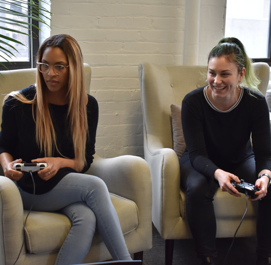 Two people smiling and playing video games