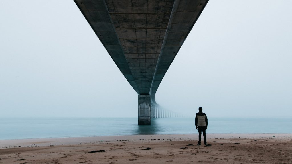 Beach-Fog-Man Standing on the Beach-Bridge-Man Standing Under a Bridge-Blue Tint-Atmospheric-Cold-Widn-Solution-Growing Business-Problems-article