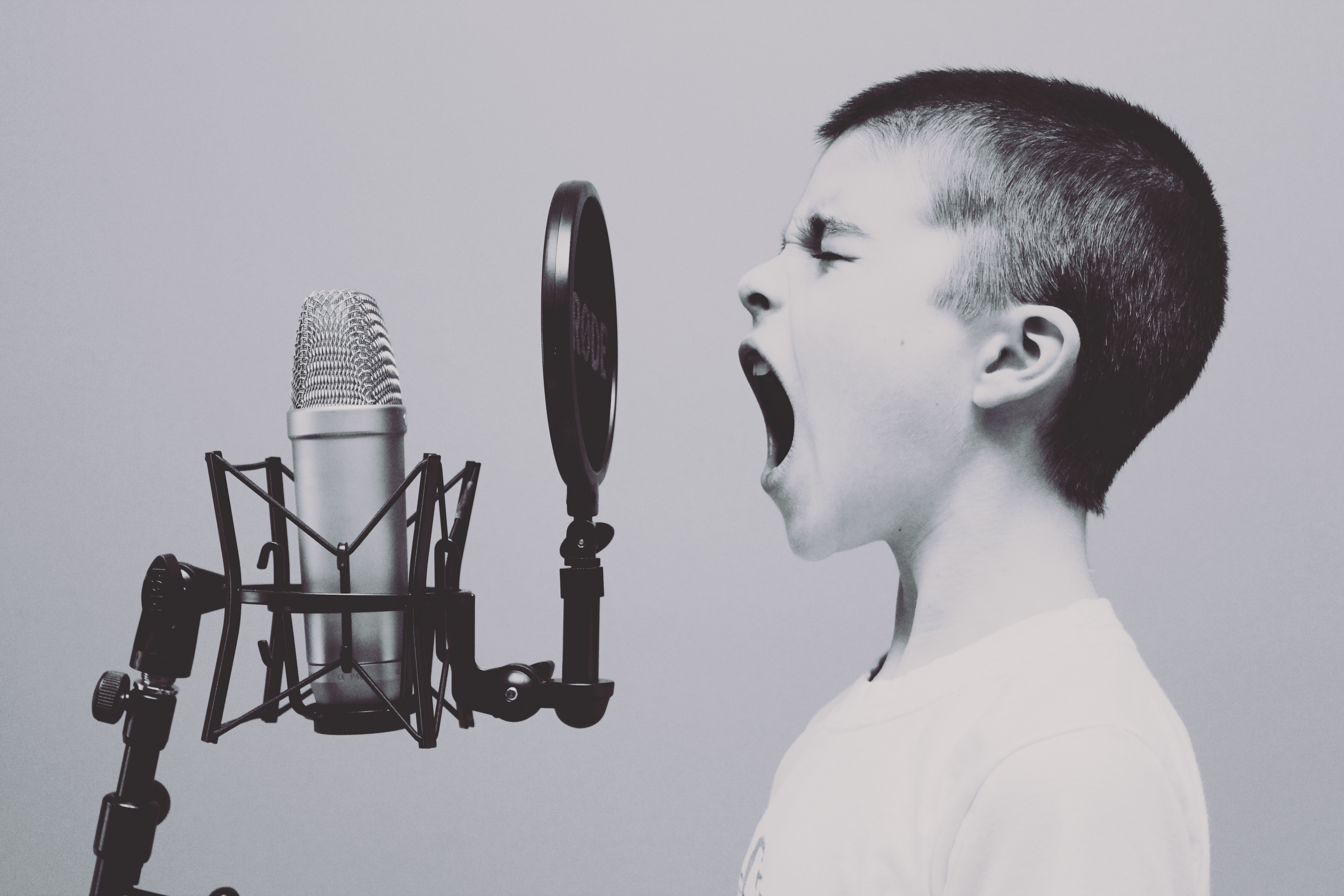 Boy screaming into microphone. Sell voiceover services online.