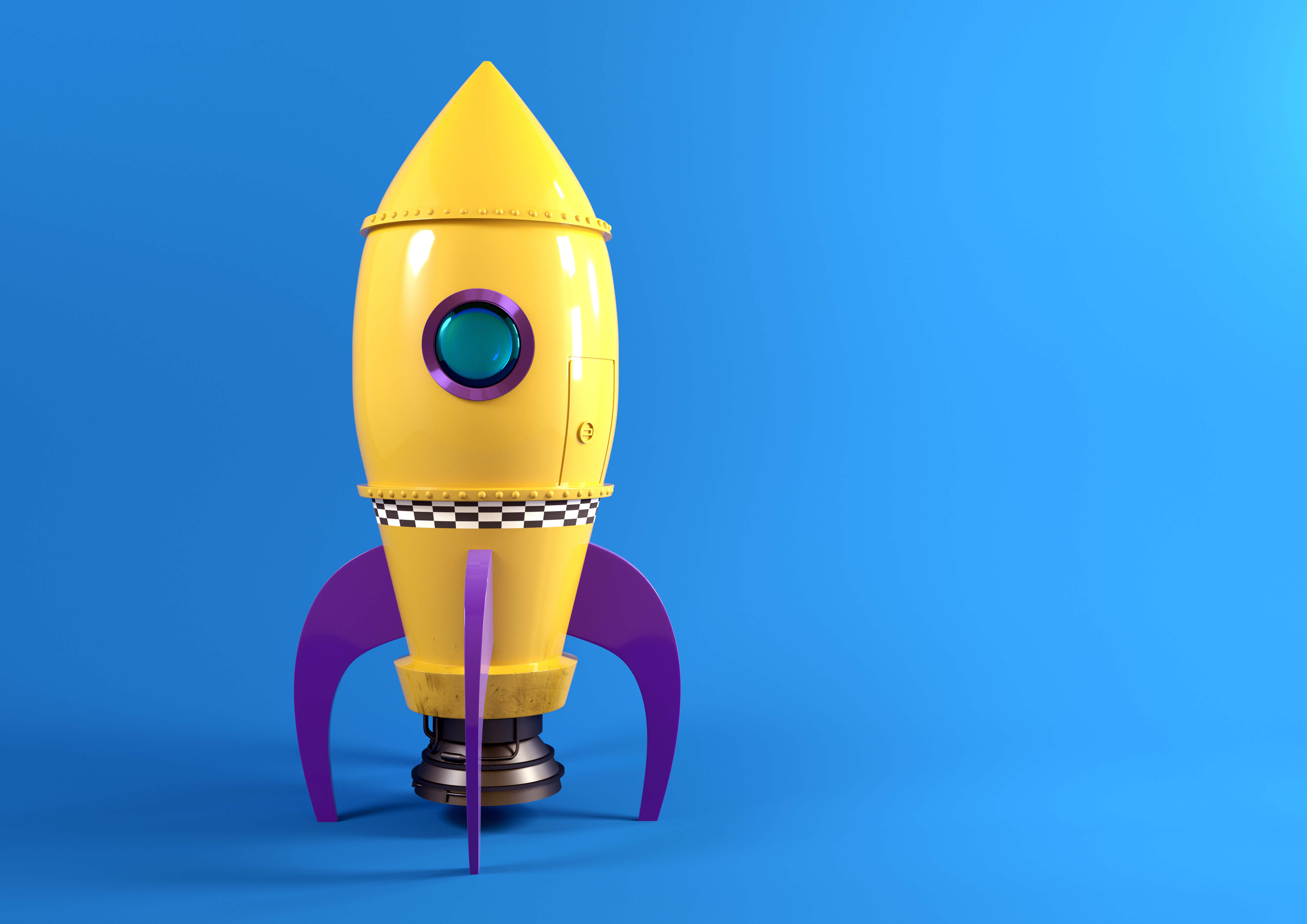 Yellow toy rocketship on blue backdrop
