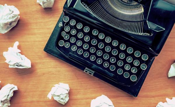 Typewriter with rolled up paper balls around it