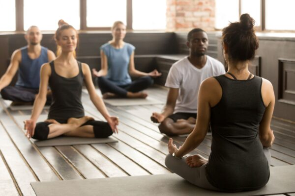 wellness consultant leading group through yoga class
