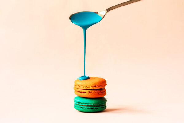 Liquid paint spills from a spoon on a macaroon
